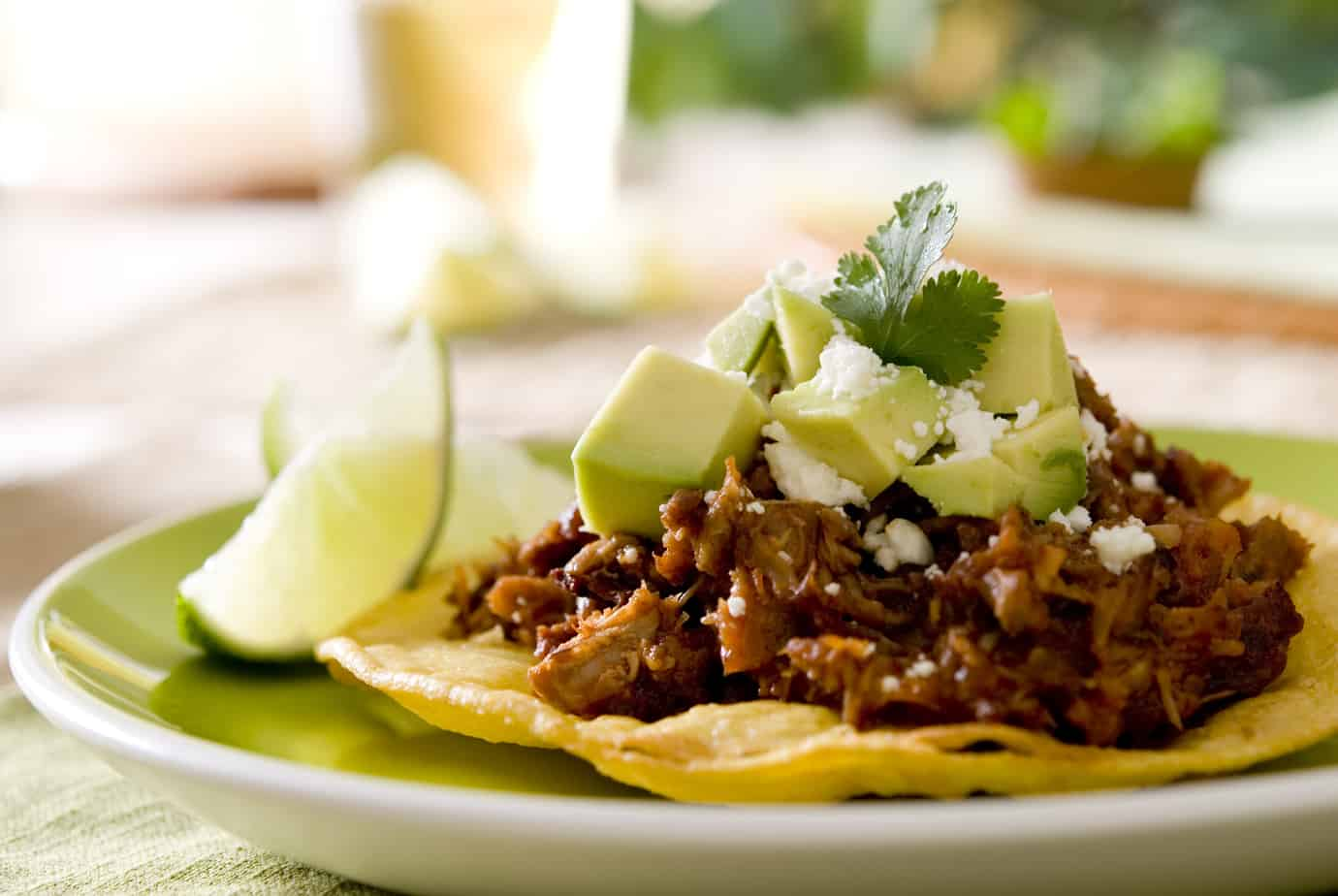 spicy beef tostada topped with guacamole and cilantro with cotija cheese