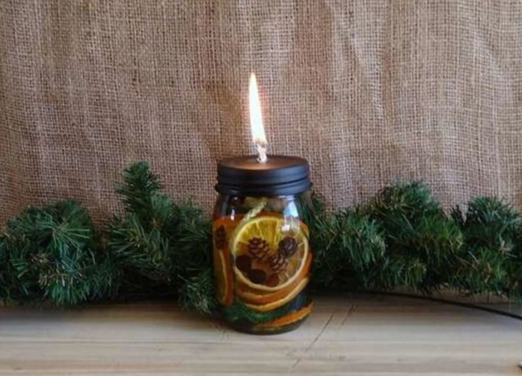 mason jar containing holiday scented fruits and pinecones