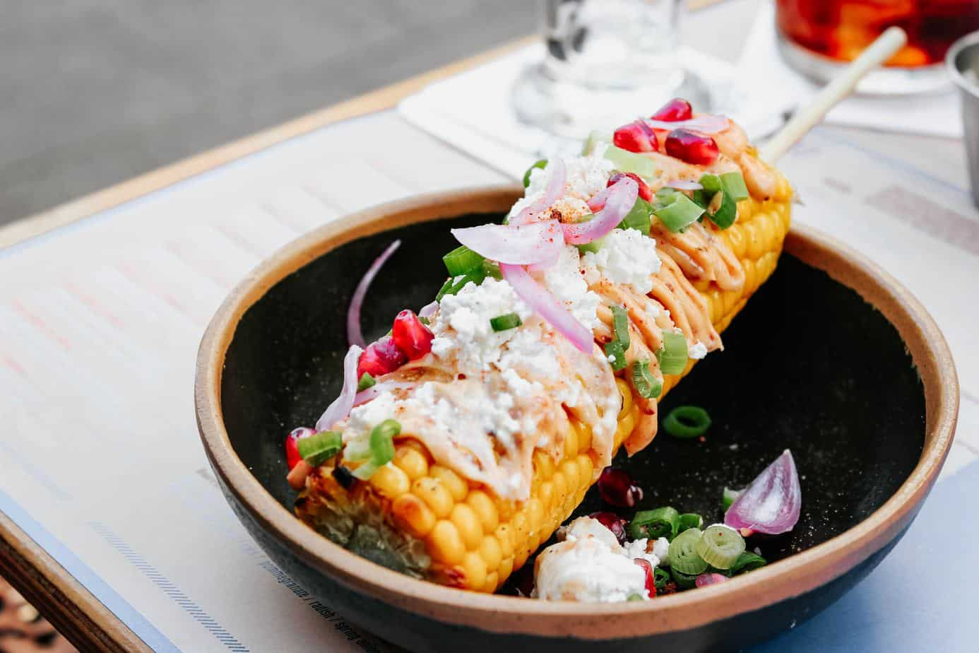 grilled mexican elotes corn on a skewer in a black ceramic bowl